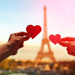 38923431 - silhouette of romantic lovers hand hold love heart paper with eiffel tower in paris with sunset